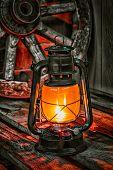 stock photo of wagon wheel  - kerosene lamp on the old wooden boards against the background wagon wheel - JPG
