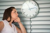 Bored executive woman looking at a clock on the wall