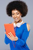 Beautiful young Afro-American woman selecting a tune on her storage device with a smile of anticipat