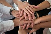 Hands of group of people stacked together as a concept of unity