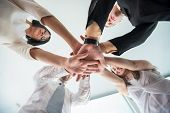 Team of business people stacking hands together