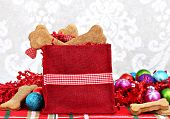 stock photo of christmas dog  - Homemade dog biscuits shaped like bones fill a festive Christmas bag - JPG