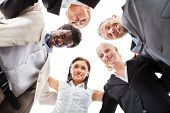 stock photo of huddle  - Low Angle View Of Multiracial Businesspeople Making Huddle - JPG