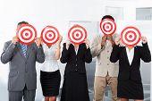 Businesspeople Holding Dartboard