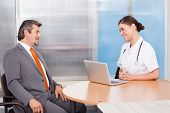 Businessman And Female Doctor Talking Together