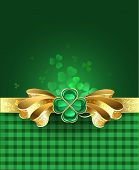image of brooch  - golden bow with a brooch in the form of a clover with four leaves on a green plaid background - JPG