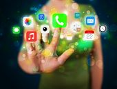 Businesswoman pressing colorful mobile app icons with bokeh background