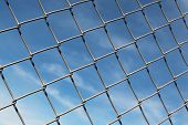 picture of chain link fence  - Chain linked fence with blue sky as background - JPG