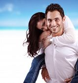 Portrait of beautiful happy couple on the beach, handsome man holding his girlfriend piggy back, rom