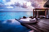 Luxury beach resort, bungalow near endless pool over sea sunset, evening on tropical island, summer