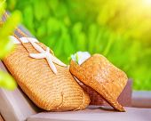 Summertime accessories, straw hat and bag decorated with starfish lying on sunbed in the garden on b