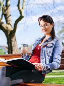 Beautiful Woman Drinking And Reading On Park Bench