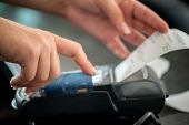 stock photo of terminator  - Hand taking receipt from pos terminal - JPG