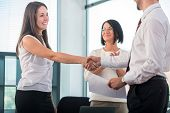 Smiling business people shaking hands at workplace