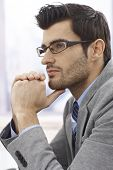 Closeup profile of thinking businessman in glasses.