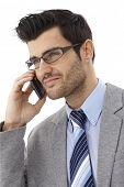 Closeup portrait of handsome businessman talking on mobilephone, wearing glasses, looking away, smil