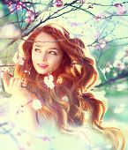 Spring beauty girl with long red blowing hair outdoors. Blooming trees. Romantic young woman portrai