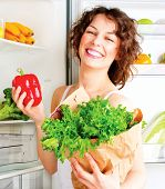 Healthy Eating Concept. Diet. Beautiful Young Woman near the Fridge with healthy food. Fruits and Ve