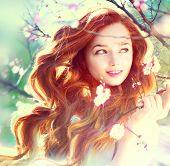 Spring beauty girl with long red blowing hair outdoors. Blooming trees. Romantic young woman portrait. Nature
