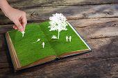Paper cut of children play on green grass book