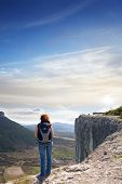 A girl standing on the edge of the high mountain and looking ahead