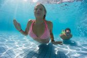 Young couple gliding underwater in the swimming pool