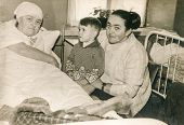 LODZ, POLAND, CIRCA 1950's: Vintage photo of mother with little son visiting bedridden grandmother i