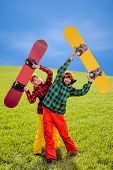 Couple In Ski Suit Having Fun With Snowboards On The Grass In Green Field