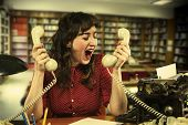 Young Woman With Red Dress Desperate With Two Telephones In Both Hands In Office