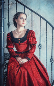 foto of stairway  - Beautiful young woman in red medieval dress on the stairway - JPG