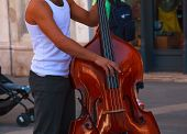 stock photo of double-bass  - View of street musician plays double bass - JPG