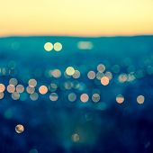 City Blurring Lights Abstract Circular Bokeh On Toned Blue Background With Horizon, Closeup
