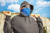 Man with a baseball bat on blue sky background