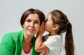 daughter whispering to mother's ear