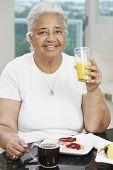 Senior African American woman eating breakfast