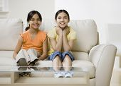 Hispanic sisters sitting on sofa