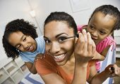 stock photo of pacific islander ethnicity  - Mixed Race sisters watching mother apply mascara - JPG