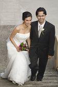 Hispanic bride and groom on steps