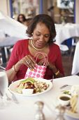 Senior African American woman opening gift bag at restaurant