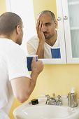 Middle Eastern man looking in mirror
