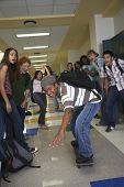 African American teenaged boy riding skateboard in school hallway