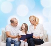 family, childhood, holidays and people - smiling mother, father and little girl reading book over blue lights background