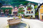 Public Drinking Water Fountain With Typical Colorful Houses In Hallstatt