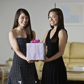Asian sisters holding gift