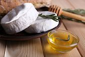 Camembert cheese on plate, bread,nuts and honey in glass bowl on wooden background