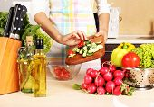 Woman cooking vegetable salad in kitchen