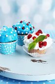 Tasty cupcakes on table, on bright background