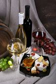 Supper consisting of Camembert and Brie cheese, honey, wine and grapes on napkin and wine barrel on