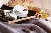 Camembert cheese on plate, nuts and bread on sackcloth on wooden background