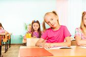 Girl sits at desk with elbows on exercise book